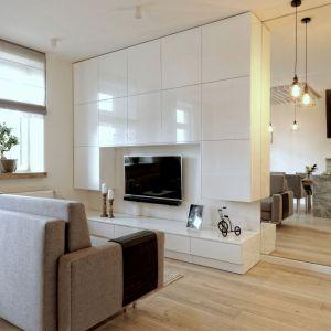 Niewielkie mieszkanie w Pile. Przestrzeń salonu wyznacza komfortowa kanapa oraz minimalistyczna zabudowa ściany za telewizorem. Obok, w lustrze odbija się zabudowa kuchni. Projekt: ewem Aranżacja wnętrz Edyta Wełnicka