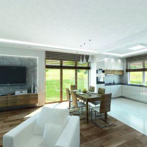 Urozmaiceniem białego minimalistycznego wnętrza jest ścianka telewizyjna pokryta betonem. Drewniana orzechowa podłoga oraz szafka telewizyjna w tym samym dekorze ocieplają strefę dzienną. Fot. Biuro Projektów MTM Styl