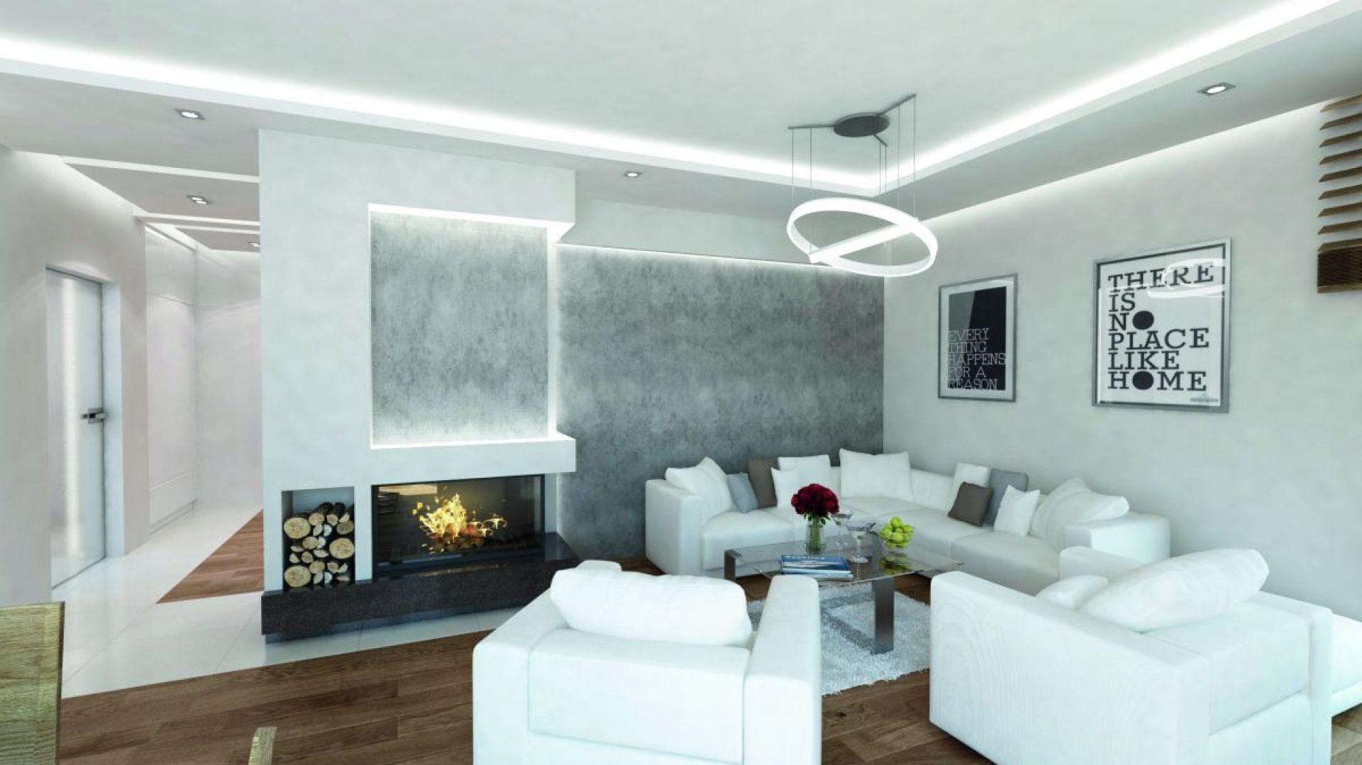Wnętrza zaprojektowano w minimalistycznym stylu. Dominują w nich biele i szarości. Centralnym punktem salonu jest strefa relaksu, którą wyposażono w białą kanapę i fotele. Fot. Biuro Projektów MTM Styl