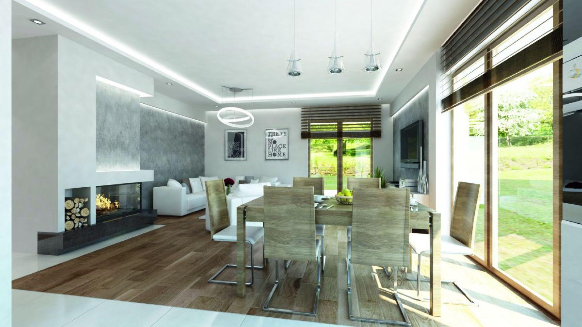 Bardzo interesująco zaprojektowano podłogę. Drewnianą posadzkę położoną centralnie w pomieszczeniu okala podłoga z białych, wielkoformatowych płytek. Fot. Biuro Projektów MTM Styl