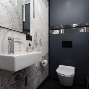 Toaleta to królestwo niestandardowych rozwiązań – zamiast płytek zastosowano tapetę winylową, a podłoga została wykończona żywicą. Projekt: Mango Studio. Fot. Przemek Kuciński
