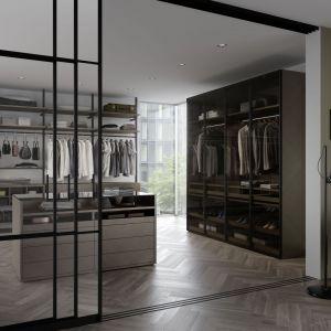 Zamontowane w półkach i drążkach oświetlenie wprowadza elegancki charakter do wnętrza, które może łączyć się z sypialnią lub łazienką. Przenikające się pomieszczenia tworzą prywatną strefę relaksu. Fot. Raumplus
