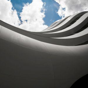 Elewację opływowego, przypominającego kroplę wody budynku pokrywa aż 5,5 tys. m kw. eleganckiego, białego Corianu. Fot. materiały prasowe OVO Wrocław