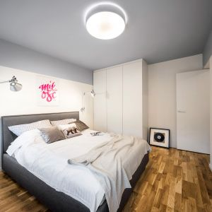Sypialnia może zaskoczyć, kiedy spodziewamy się równie mocnych akcentów kolorystycznych – trafiamy na biel i ciepły odcień szarości, który idealnie komponuje się z drewnianą podłogą. Projekt: 3XEL Architekci. Fot. Paweł Augustyniak