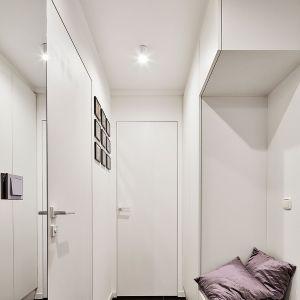 Niewielkie mieszkanie o powierzchni niespełna 40 m² otwiera jasny hol wejściowy z pojemną szafą oraz siedziskiem. Projekt: 3XEL Architekci. Fot. Paweł Augustyniak