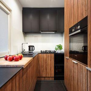 Mała kuchnia mieści wszystkie niezbędne sprzęty AGD oraz pralkę w zabudowie. Niewielka przestrzeń została w pełni wykorzystana poprzez wysoką zabudowę meblową. Pionowo ułożona faktura drewna nadaje pomieszczeniu strzelistości. Projekt: 3XEL Architekci. Fot. Paweł Augustyniak