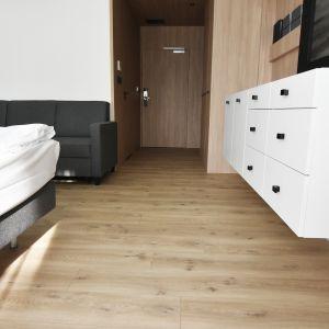 Podłoga jako element dekoracji wnętrza hotelowego może harmonizować z wizerunkiem marki lub podkreślać urok i charakter niezwykłej lokalizacji. Na zdjęciu realizacja hotelowa z zastosowanymi podłogami Pergo. Hotel Harmony Winyl – podłoga winylowa. Restauracja oraz pokoje: podłoga w kolorach drewna z kolekcji Modern Plank.Fot. Pergo