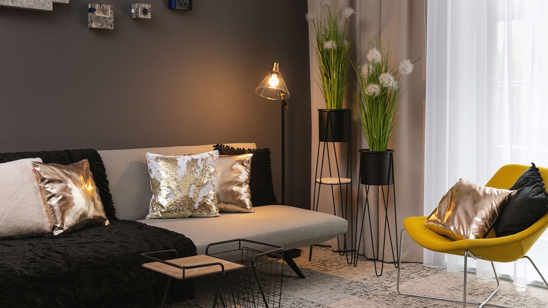 Gold - elegancja i luksus tej aranżacji tkwią w prostocie, a zestawienia różnych odcieni złota komponują się harmonijnie dzięki kontrastowej czerni i przestronności apartamentu. Stylizacja: Home&You. Fot. Przemysław Długokiński