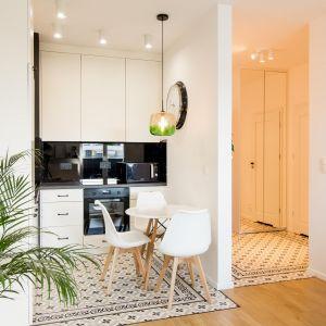 Architekci postanowili oddzielić przestrzeń salonu, kuchni i korytarza wejściowego podłogą. W kuchni i przedpokoju znajdziemy wzorzyste płytki podłogowe, a w salonie drewnianą podłogę. Projekt: The Space. Fot. Piotr Czaja