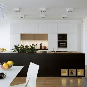 """Kuchnię zaprojektowano tak, by nieco zgubić jej """"kuchenny"""" charakter. Na podłodze, zamiast tradycyjnych płytek położono dębowe deski (te same co w całym salonie), a większość górnych szafek pozostawiono w bieli, by nie konkurowały z resztą pomieszczenia. Fot. Inter Arch"""