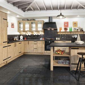 Kamienny blat i ozdobny dekor na ścianie idealnie wpisały się w klimat retro kuchni Kamelia z systemu KAMplus z postarzanymi frontami i stylizowanymi okuciami. Fot. KAM