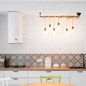 Aby nie zmniejszać wizualnie przestrzeni, zrezygnowano z wiszących szafek kuchennych na głównej, widocznej od strony salonu ścianie. Wykończona białą cegłą oraz dekoracyjnymi, patchworkowymi płytkami ściana, pełni funkcję reprezentacyjną. Projekt i nadzór Monika Staniec. Fot. Łukasz Bera
