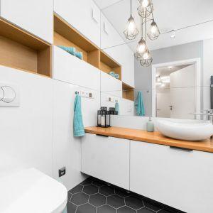 Dzięki przeniesieniu pralki, łazienka zyskała na przestronności na tyle, że udało się w niej zmieścić dużą wannę, a także umywalkę stojącą na obszernej szafce z laminowanym blatem i podwieszaną toaletę. Projekt i nadzór Monika Staniec. Fot. Łukasz Bera