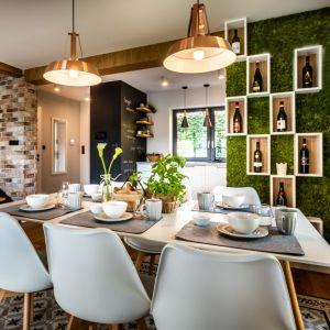 Aby podkreślić związek z przyrodą, projektantka wprowadziła do wnętrza zieleń w postaci ściany z mchu skandynawskiego, w którą wkomponowano półki na wino. Projekt: Małgorzata Szpak. Fot. Lukas Patecki