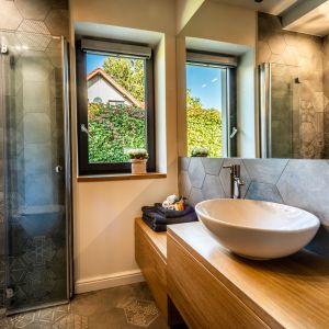 Dzięki zastosowaniu składanych drzwi kabiny prysznicowej, projektantce udało się w niewielkiej łazience na parterze zmieścić odkurzacz centralny, piec gazowy i pralkę. Projekt: Małgorzata Szpak. Fot. Lukas Patecki