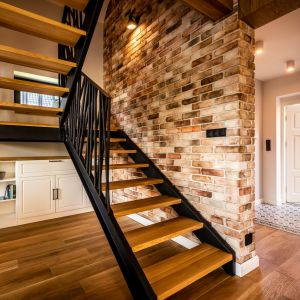 Elementy industrialne, takie jak surowa cegła na ścianie czy stalowe schody z ażurową balustradą i dębowymi stopniami, świetnie wzbogacają wnętrza i nadają im indywidualny charakter. Projekt: Małgorzata Szpak. Fot. Lukas Patecki
