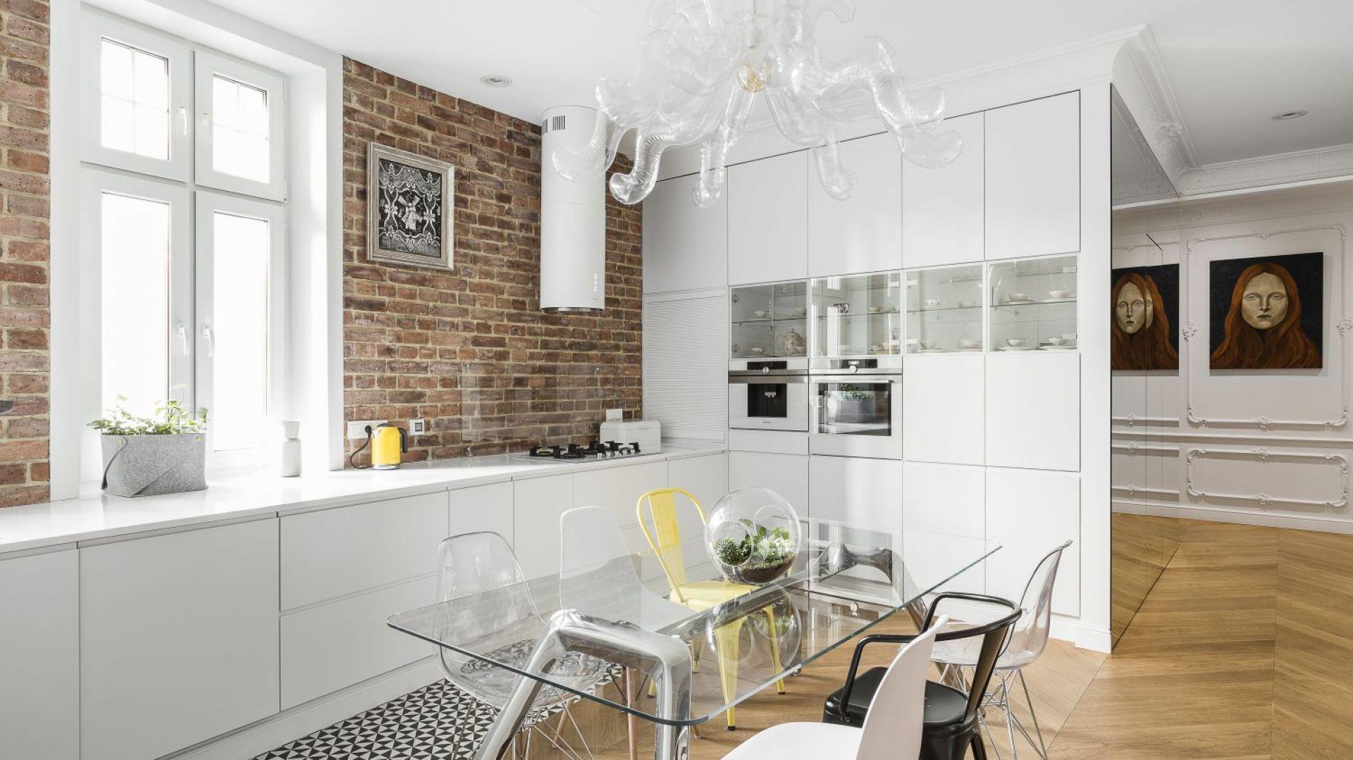 W kuchni z czerwoną cegłą kontrastuje minimalistyczna biała zabudowa. Projekt: Anna Maria Sokołowska. Fot. Foto&Mohito