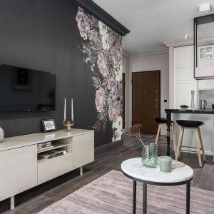 Kwiatowe motywy oraz zaczerpnięte z wzoru tapety odcienie różu pojawiają się w postaci dodatków w salonie. Projekt: JT Grupa. Zdjęcia: Foto&Mohito