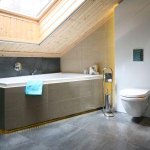 Małe łazienki przeważnie umiejscowione są na poddaszu, gdzie ograniczeniem są również skosy. Tu ścianę dachową wykończono drewnem i podświetlono wannę, co nadało łazience niepowtarzalnego uroku. Projekt: Tomasz Motylewski, Marek Bernatowicz. Fot. Bartosz Jarosz