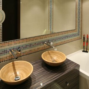 Duże lustro obudowane kolorową mozaiką wprowadza ciekawą kolorystykę do małej łazienki i dodatkowo optycznie ja powiększa. Projekt: Agnieszka Ludwinowska. Fot. Bartosz Jarosz
