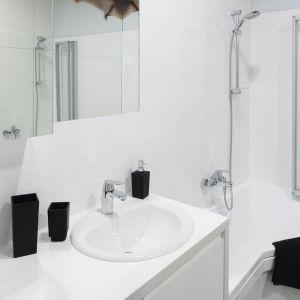 Małą łazienkę w bieli doskonale ożywiają dodatki w czarnym kolorze. Projekt: Tomasz Jasiński/Nowa Papiernia. Fot. Bartosz Jarosz