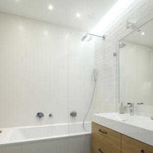W tej niewielkiej łazience urządzonej w bieli zastosowano rozwiązanie 2w1, czyli prysznic połączony z wanną, co na małych przestrzeniach doskonale się sprawdza. Projekt: Agnieszka Żyła. Fot. Bartosz Jarosz