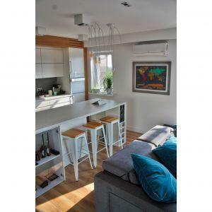 Połączona z salonem niewielka kuchnia została zaprojektowana tak, aby mogła spełniać jak najwięcej funkcji. Projekt: Barbara Uherek-Bradecka (Studio BB Architekci). Fot. Paweł Nawrot