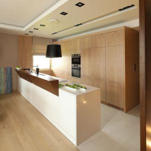Duży, funkcjonalny półwysep z lakierowanego na biało MDF-u stanowi część roboczą kuchni. Jego blat dyskretnie przesłaniają oryginale drewniane nadstawki. Projekt: Laura Sulzik. Fot. Bartosz Jarosz