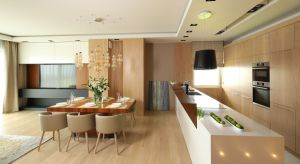 Centralną część otwartej strefy dziennej stanowi jadalnia, której wyjątkową ozdobą jest dekoracyjna lampa nad stołem. Wykonana z dmuchanego szkła w bursztynowym kolorze, niczym korale ozdabia powściągliwą aranżację kuchni.