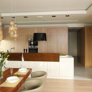 Kuchnia otwarta połączona z jadalnią jest reprezentacyjna i przytulna zarazem. Projekt: Laura Sulzik. Fot. Bartosz Jarosz