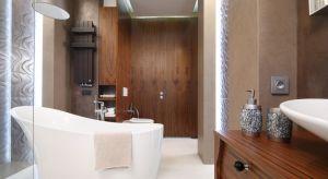 Elegancka łazienka przy sypialni oferuje możliwość kąpieli w luksusowej wannie lub kabinie walk-in. Nastrojowe oświetlenie, subtelne odcienie brązów oraz płytki z efektem 3D tworzą scenerię idealną do relaksu.