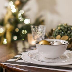W przypadku jadalni niezwykle ważne jest odpowiednie nakrycie stołu. Możemy wykorzystać do tego białą porcelanę ze złotymi zdobieniami.  Fot. Pracownia KODO
