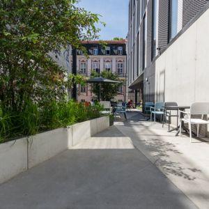Biurowiec Za Bramką, Poznań, Ultra Architects. Lokalizacja obiektu była głównym czynnikiem determinującym jego formę.  Front budynku tworzy spokojna, współczesna kompozycja z wieloma przeszkleniami, która pozwoliła na harmonijne wpisanie elewacji w miejską pierzeję. Fot. materiały prasowe