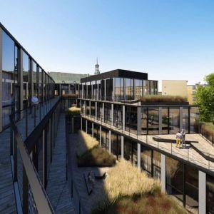 Biurowiec Za Bramką, Poznań, Ultra Architects. Ograniczona przestrzeń sprawiła, że od strony dziedzińca każdą z kondygnacji cofnięto względem poprzedniej, tworząc w ten sposób drewniane tarasy z zielenią. Fot. materiały prasowe