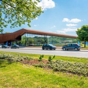 Hala 100-lecia KS Cracovia 1906 wraz z Centrum Sportu Niepełnosprawnych, Kraków, Biuro Projektów Lewicki Łatak Szucha. Budynek o horyzontalnej bryle jest kontynuacją topograficznej rzeźby terenu.  Obiekt został zintegrowany z otoczeniem poprzez stworzenie wału, na którego szczycie zaprojektowano pochylnię prowadzącą na dach. Wysokość budynku wynosi 16,48 m. Elewację pokrywają głównie panele z blachy Cor-Ten – stali o specjalnym składzie chemicznym zapewniającym odporność na korozję i charakterystyczne rdzawe zabarwienie. Fot. materiały prasowe