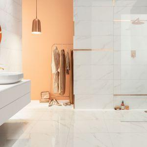 Kolekcję płytek ściennych, podłogowych i dekorów Serenity (33x90 cm) o wzorze marmuru carrara uzupełnia listwa ścienna w kolorze miedzi. Fot. Tubądzin