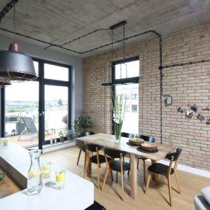 Industrialny styl wnętrz podkreśla poprowadzone na powierzchni ścian i sufitu okablowanie oświetlenia. Projekt: Maciejka Peszyńska-Drews. Fot. Bartosz Jarosz