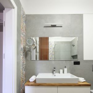 W łazience do loftowej stylistyki nawiązują szare płytki jak beton, które zestawiono tutaj z kolorową trójwymiarową glazurą. Projekt: Maciejka Peszyńska-Drews. Fot. Bartosz Jarosz