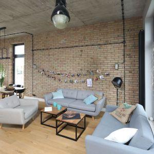 W konwencję loftową wpisują stylowe poduszki wykonane z worków po kawie czy też czarne, okrągłe kontakty na ścianach. Projekt: Maciejka Peszyńska-Drews. Fot. Bartosz Jarosz