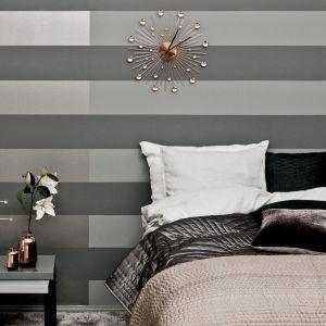 Efektowne pasy na ścianie za łóżkiem tworzą dwa odcienie szarości farby Tikkurila Optiva Matt 5. Fot. Tikkurila