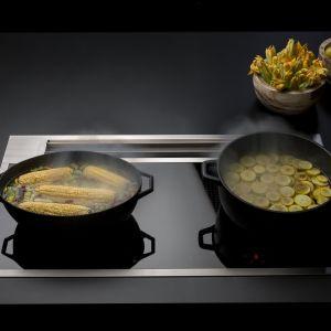 Okap nablatowy Sintesi ze zintegrowaną płytą grzewczą pochłania kuchenne opary już na poziomie naczyń. Fot. Flamec
