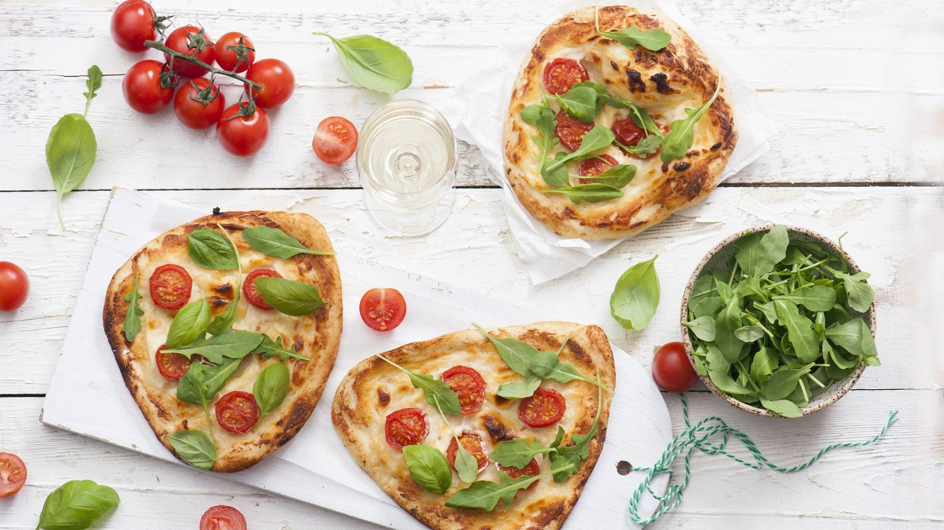 Mini pizza z topionym serkiem, pomidorami i rukolą. Fot. Hochland
