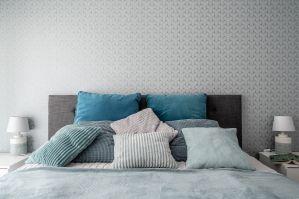 Dobrym pomysłem jest stworzenie unikalnego tła w postaci wzorzystej, oryginalnej tapety i ciemniejszego wezgłowia łóżka. Surowe szarości przełamują natomiast tkaniny i poduszki – o różnej fakturze, w kolorze mniej lub bardziej stonowanego turkusu. Projekt: Pracownia KODO Projekty i Realizacje. Fot. KODO