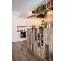 Tło dla drewnianych mebli w postaci półek czy zabudowy oddzielającej kuchnię od jadalni stanowi biel. Projekt: Pracownia KODO Projekty i Realizacje. Fot. KODO