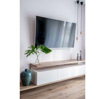 Projektantki zrezygnowały z zabudowy ściany pod TV na rzecz szafki, oświetlenia dekoracyjnego, które znalazło także zastosowanie w strefie wypoczynku, oraz roślin i turkusowych dekoracji. Projekt: Pracownia KODO Projekty i Realizacje. Fot. KODO