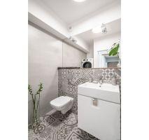 Niewielką toaletę powiększają optycznie lustra, z kolei białe fronty zabudowy umywalkowej to harmonijne nawiązanie do mebli zastosowanych w pozostałych pomieszczeniach. Projekt: Pracownia KODO Projekty i Realizacje. Fot. KODO