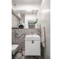 Wydzielone pomieszczenie z toaletą pełni także funkcję pralni. Mieszkańcy zdecydowali się na wygodne rozwiązanie – pralka i suszarka ustawione jedna na drugiej. Projekt: Pracownia KODO Projekty i Realizacje. Fot. KODO