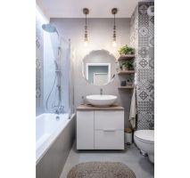 Minimalistyczny charakter łazienki przełamują płytki z hiszpańskim motywem oraz drewno – w postaci blatu pod umywalką, półek czy lamp. Projekt: Pracownia KODO Projekty i Realizacje. Fot. KODO