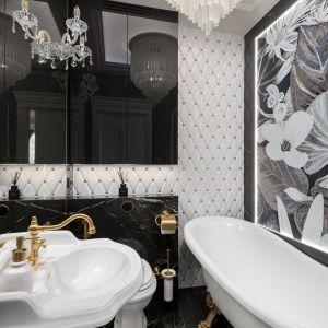 Charakter łazienki buduje kontrast między czernią a bielą, który został przełamany złotymi dodatkami. Projekt: Agnieszka Hajdas-Obajtek. Fot. Wojciech Kic