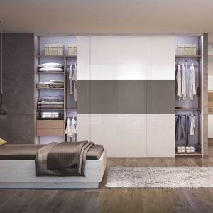 Idealnym pomysłem na ergonomiczne zagospodarowanie niewielkiej sypialni jest wykorzystanie szafy z drzwiami przesuwnymi w dopasowanym kolorze, która doskonale zastąpi komodę, mieszcząc w sobie nie tylko ubrania, ale również bieliznę pościelową, koce czy ręczniki. Fot. Komandor
